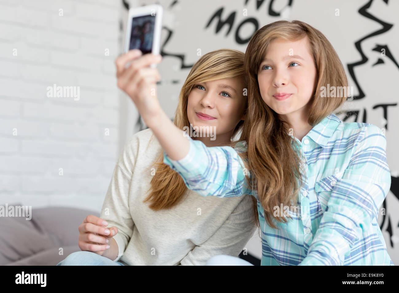 Nette Schwestern fotografieren mit Ihrem Smartphone zu Hause Stockbild