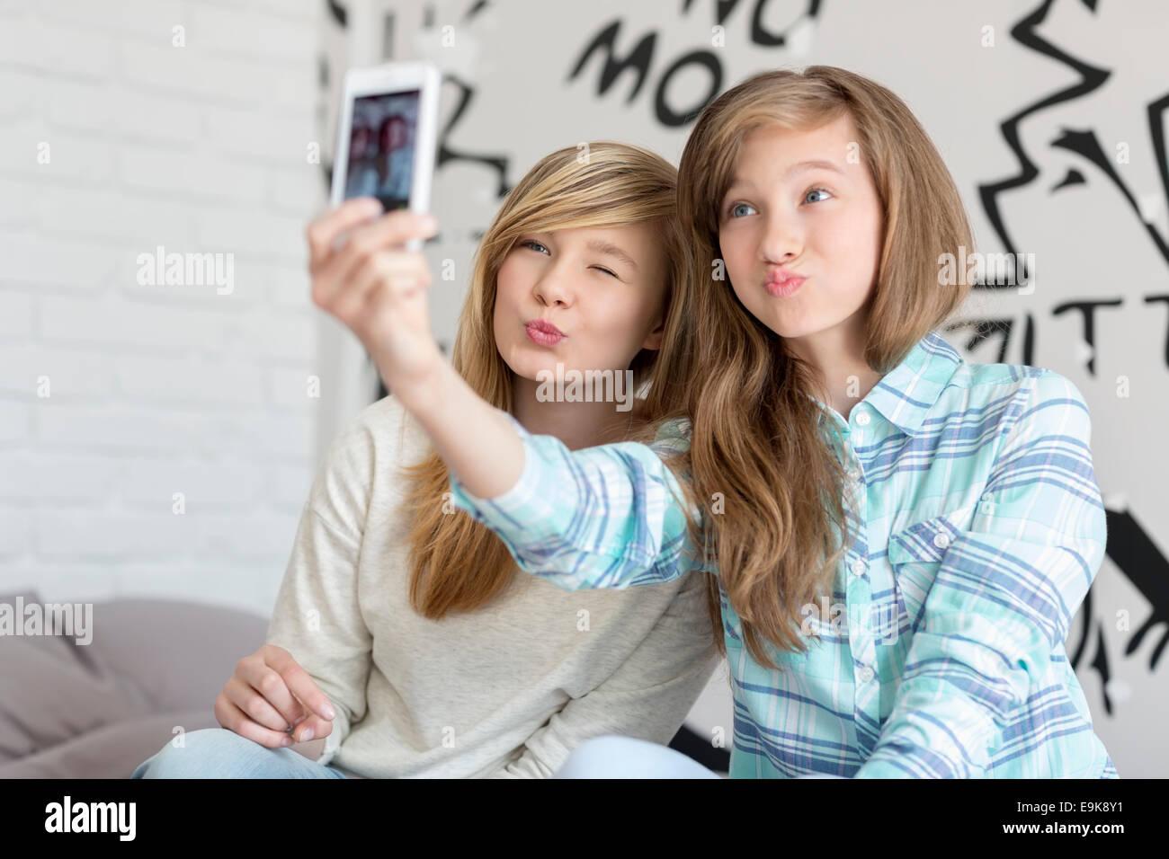 Nette Schwestern schmollend beim Fotografieren mit Ihrem Smartphone zu Hause Stockbild
