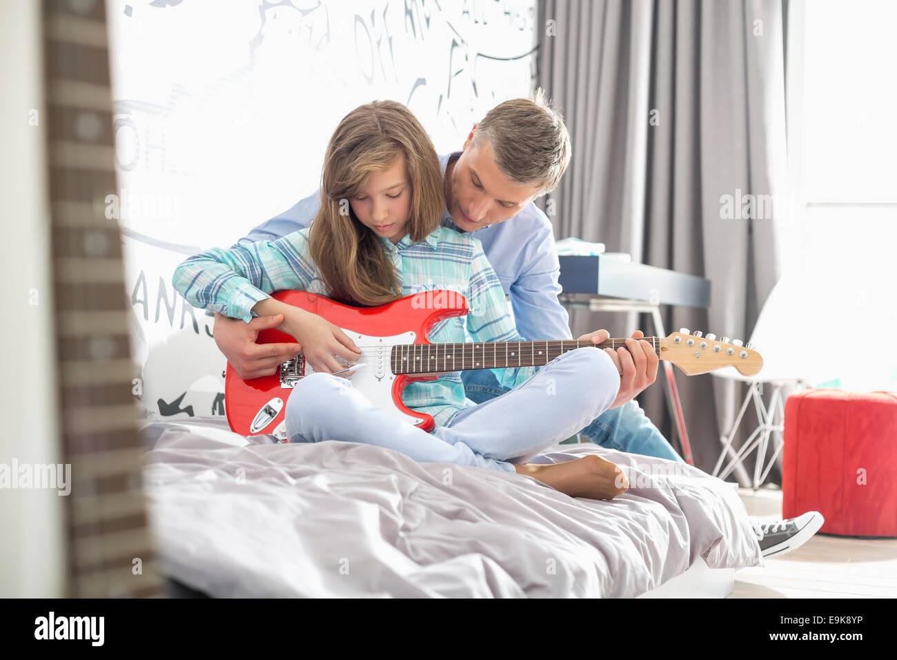 Vater Lehre Tochter zu Hause Gitarre spielen Stockbild