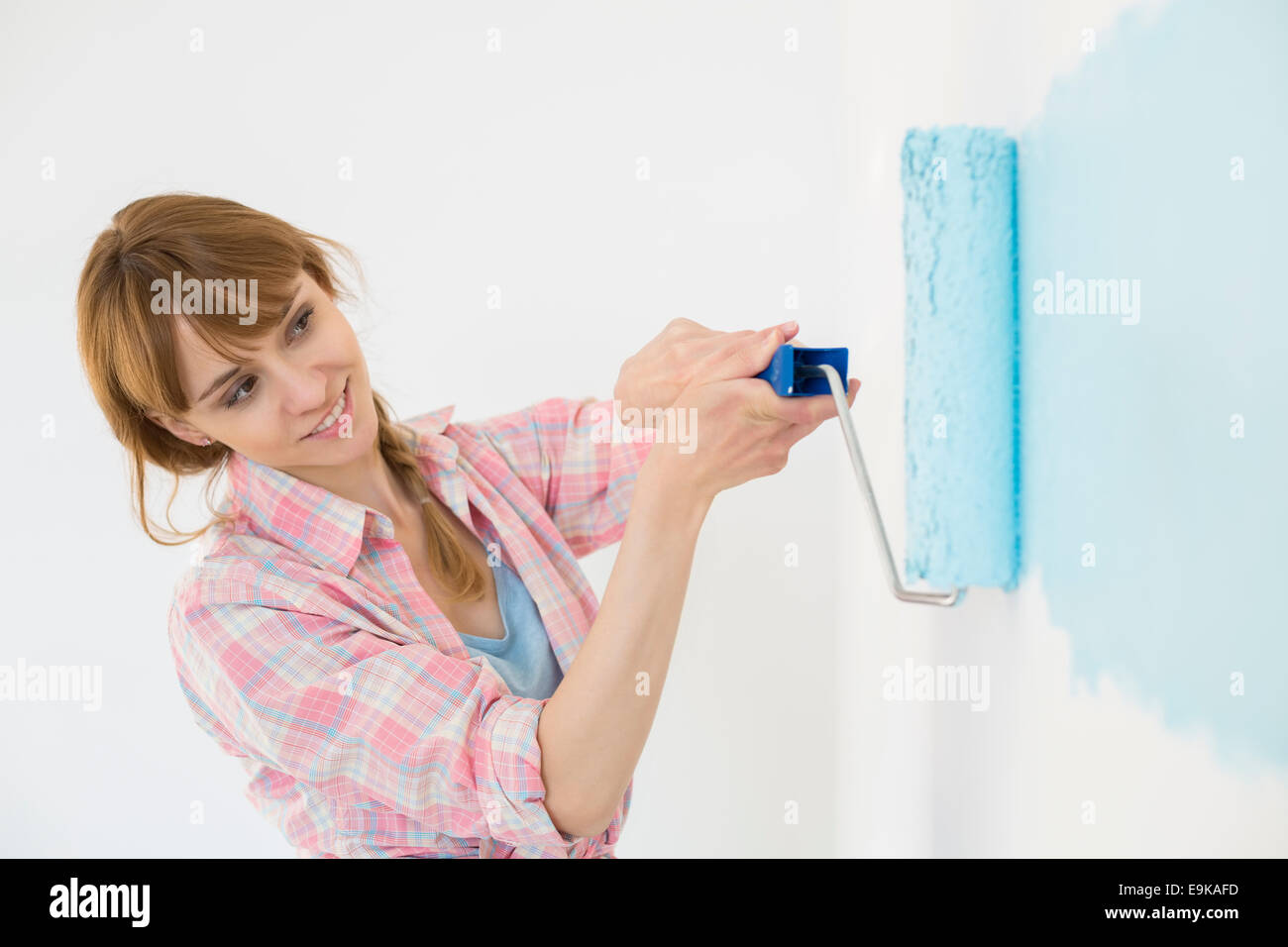 Schöne Frau Malerei Wand mit Farbroller Stockbild
