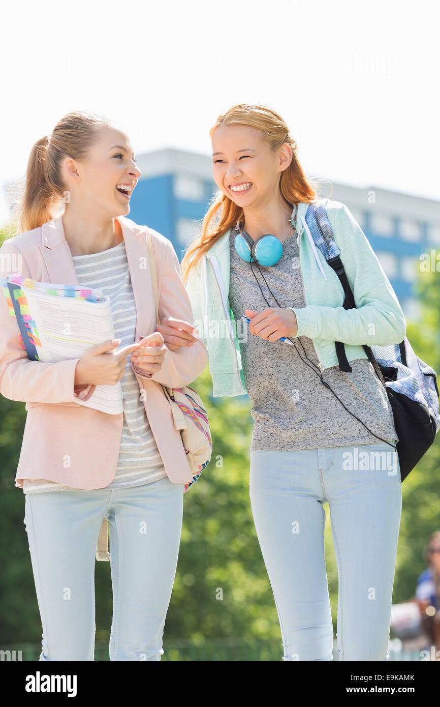 Fröhliche junge Studentinnen zu Fuß auf dem campus Stockbild
