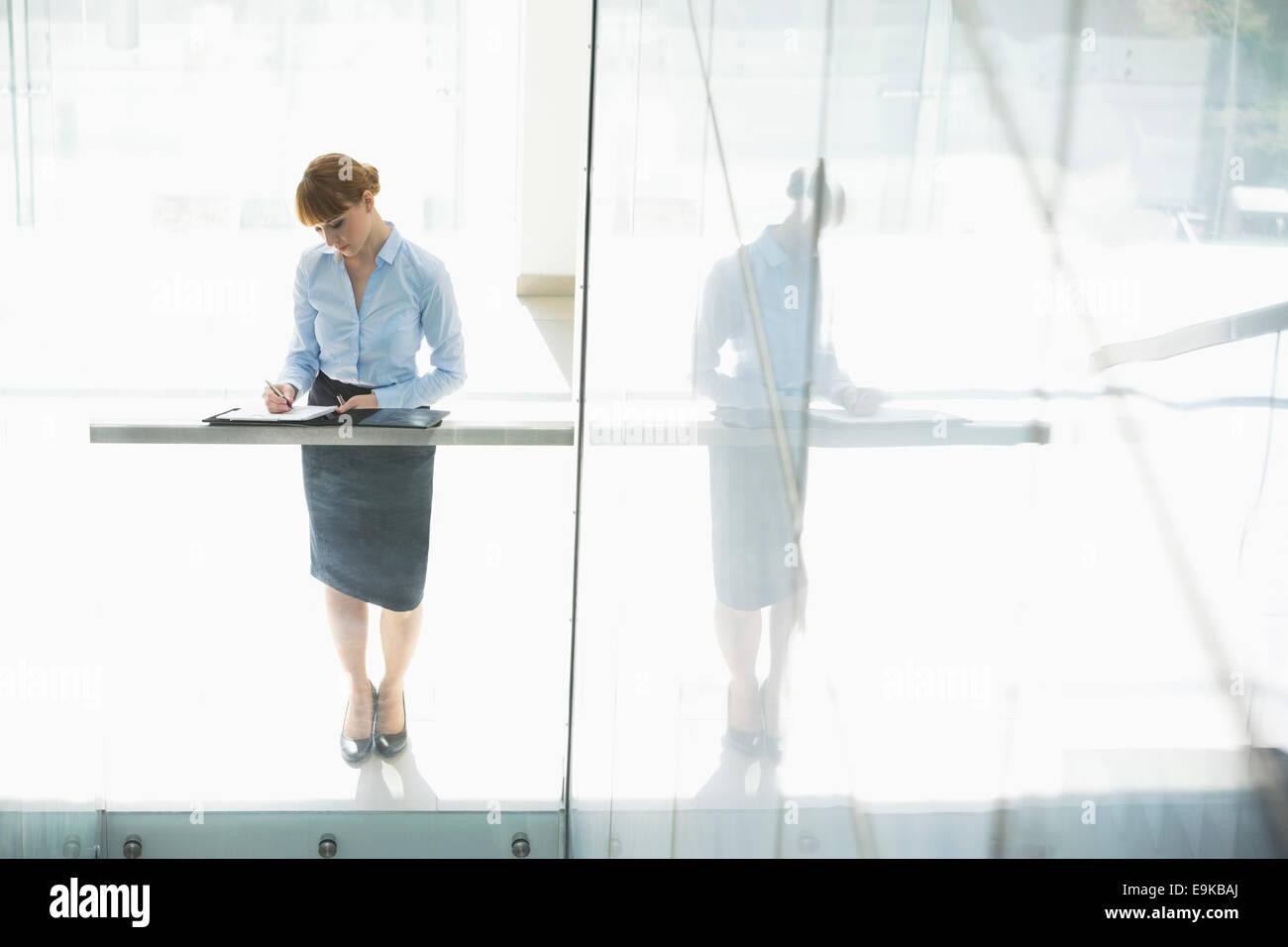 In voller Länge der Geschäftsfrau auf Dokument in Office schreiben Stockbild