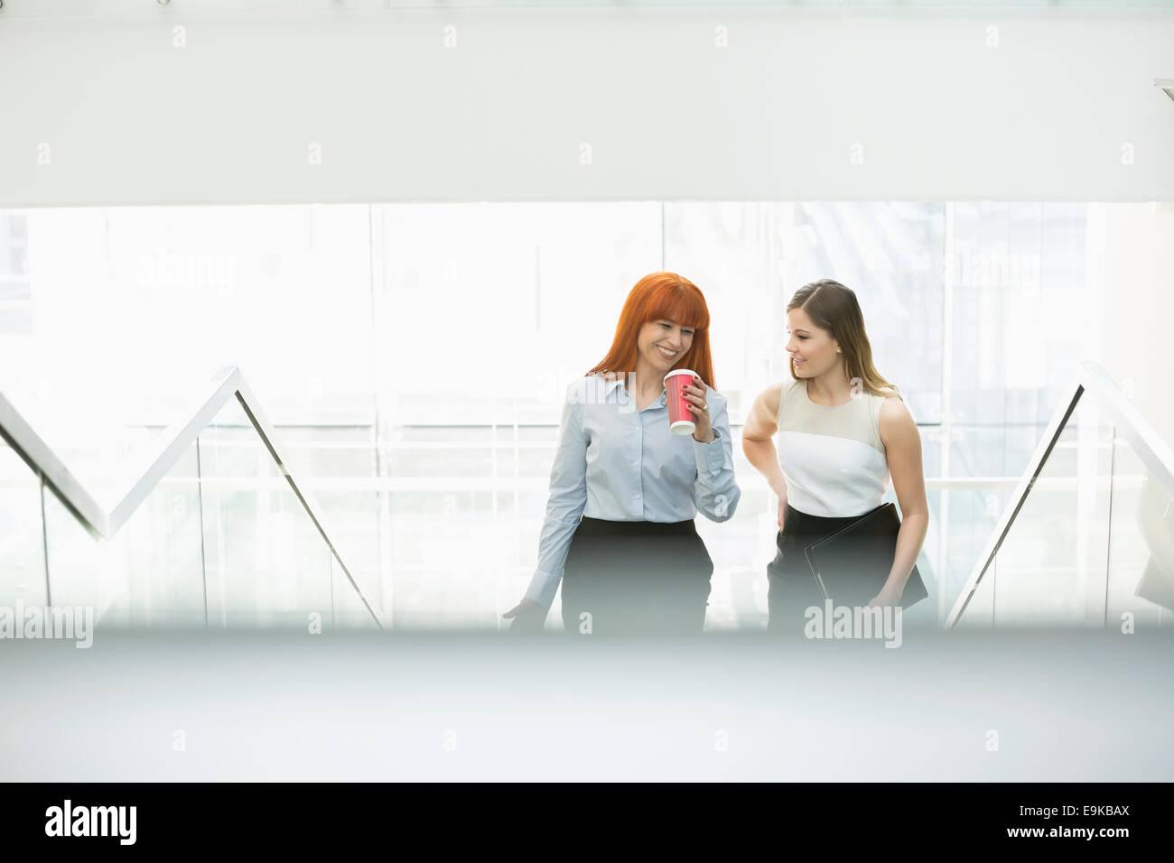 Geschäftsfrauen Kaffeetrinken während der Bewegung Stufen im Büro Stockbild