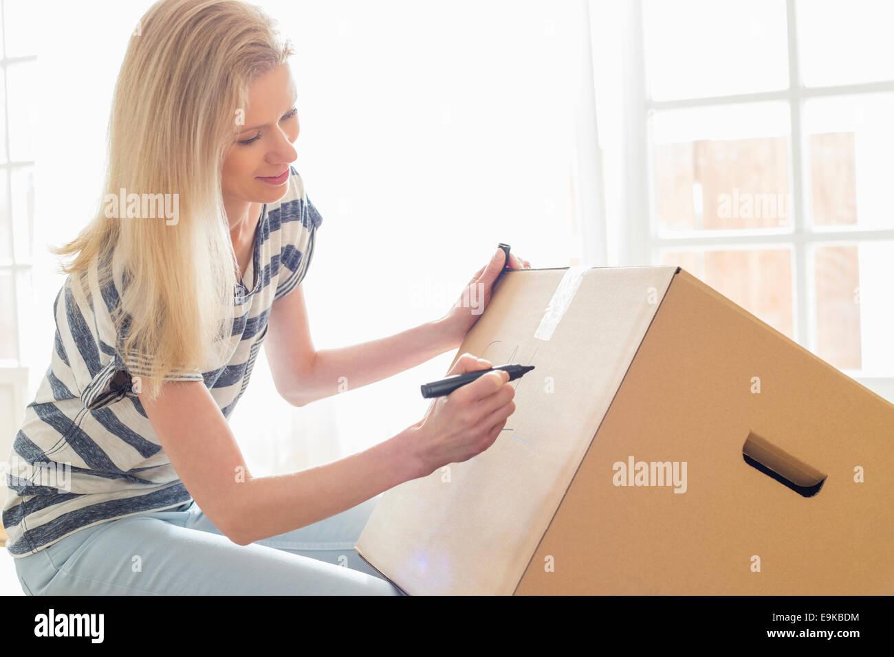 Frau zu Hause Umzugskarton Beschriftung Stockbild