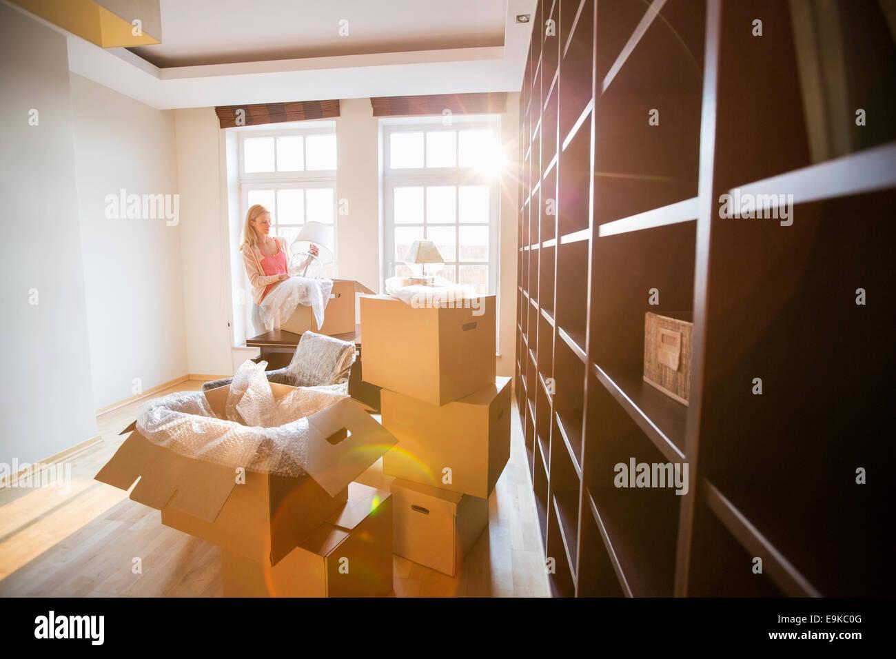 Frau Lampe von beweglichen Box im neuen Haus Auspacken Stockbild