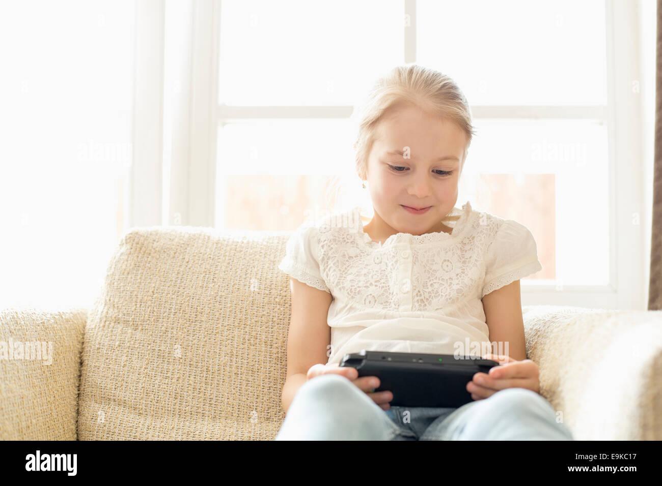 Niedliche Mädchen tragbare Videospiel zu Hause spielen Stockbild