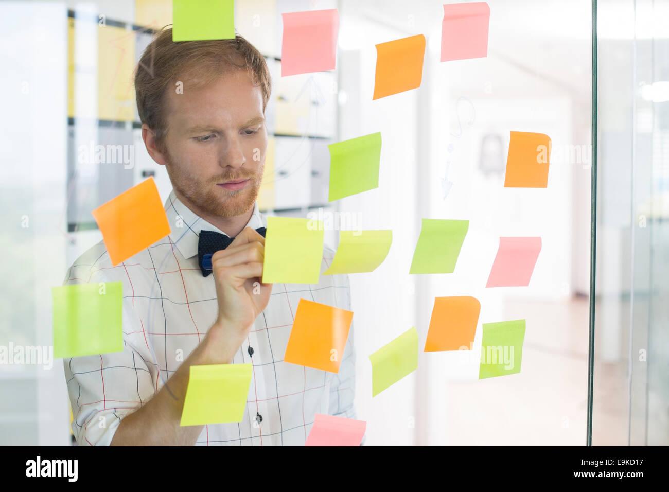 Kreative Unternehmer schriftlich auf klebrigen Papier im Büro Stockbild