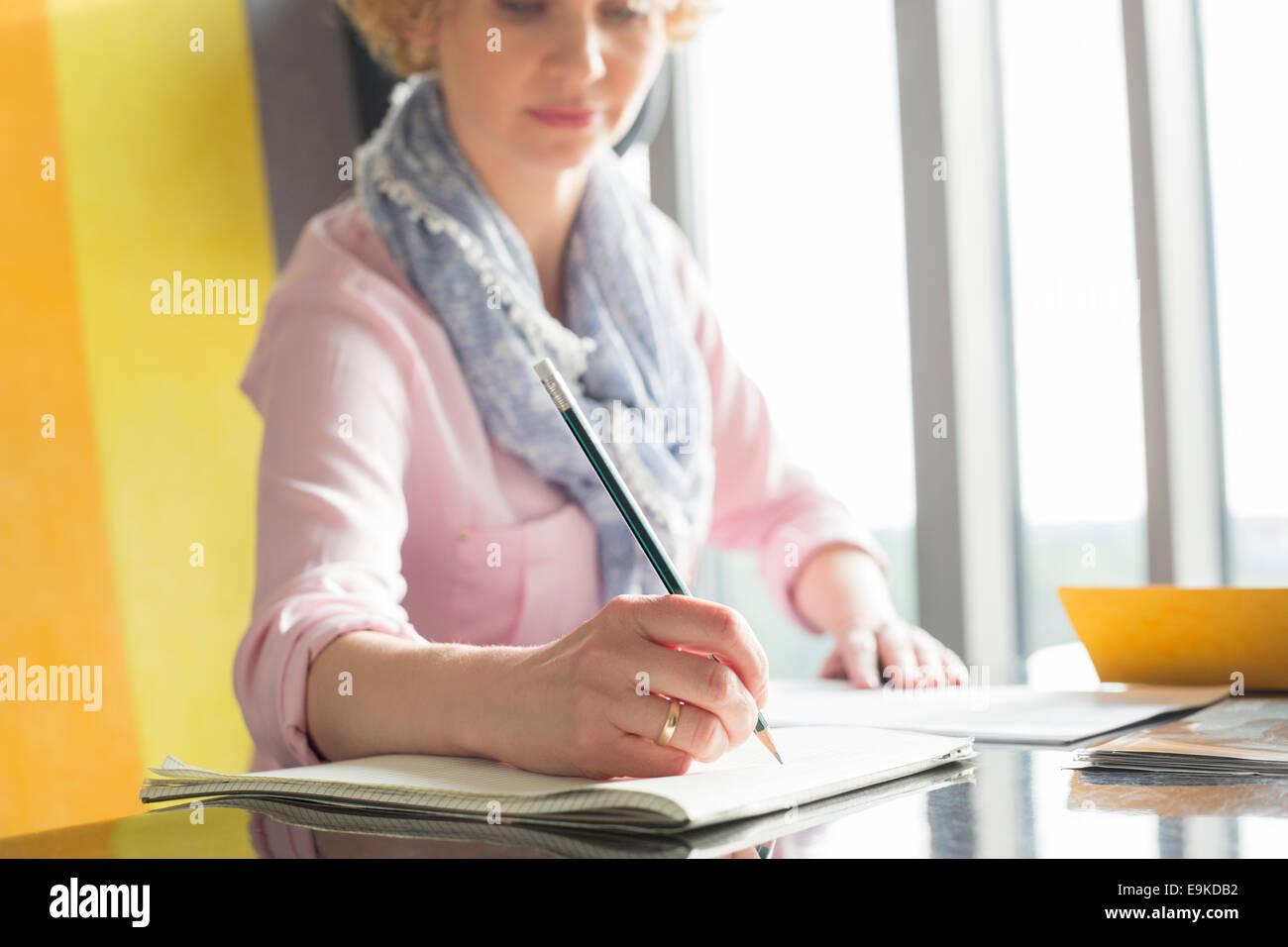 Mitte adult Geschäftsfrau auf Merkzettel am Schreibtisch im Büro schreiben Stockbild