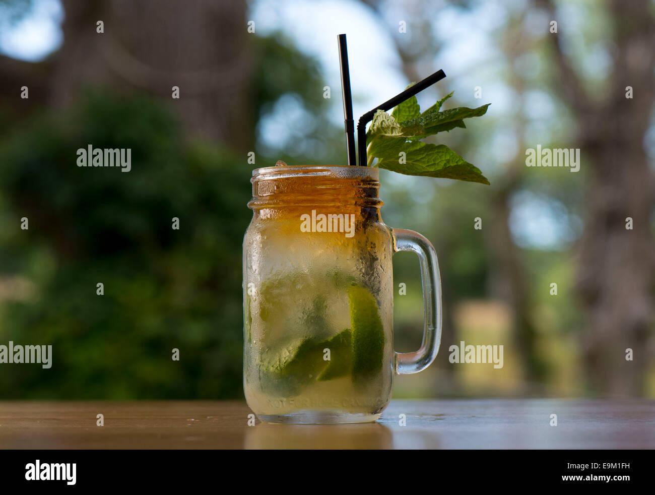 Ein Mojito Rum cocktail mit einem grünen Hintergrund. Stockbild