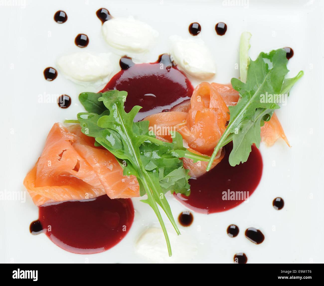 Geräucherter Lachs Graved Lachs als Vorspeise auf einem weißen Teller mit Chilisauce serviert. Stockbild