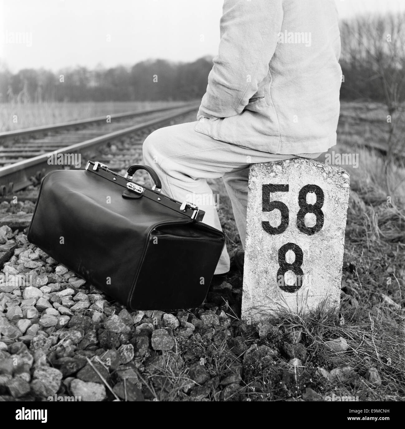 Eine Person mit einer Tasche sitzt neben Bahngleisen Stockbild