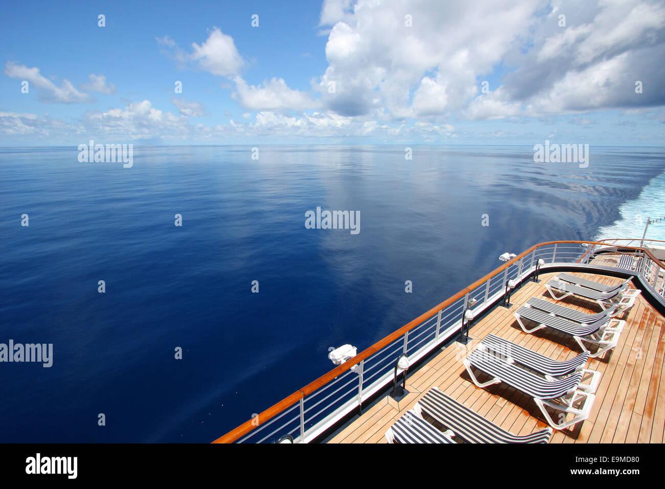 Kreuzfahrtschiff fährt über eine schöne ruhige Meer. Liegestühle ...