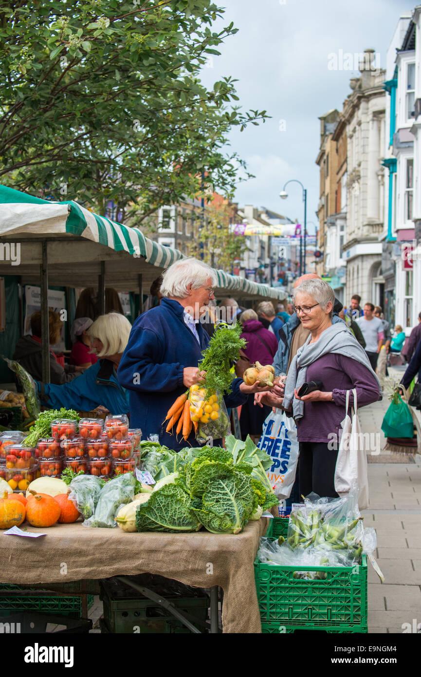 Menschen beim Einkaufen für frisches Gemüse an der Aberystwyth Farmers Market, Wales, UK Stockbild