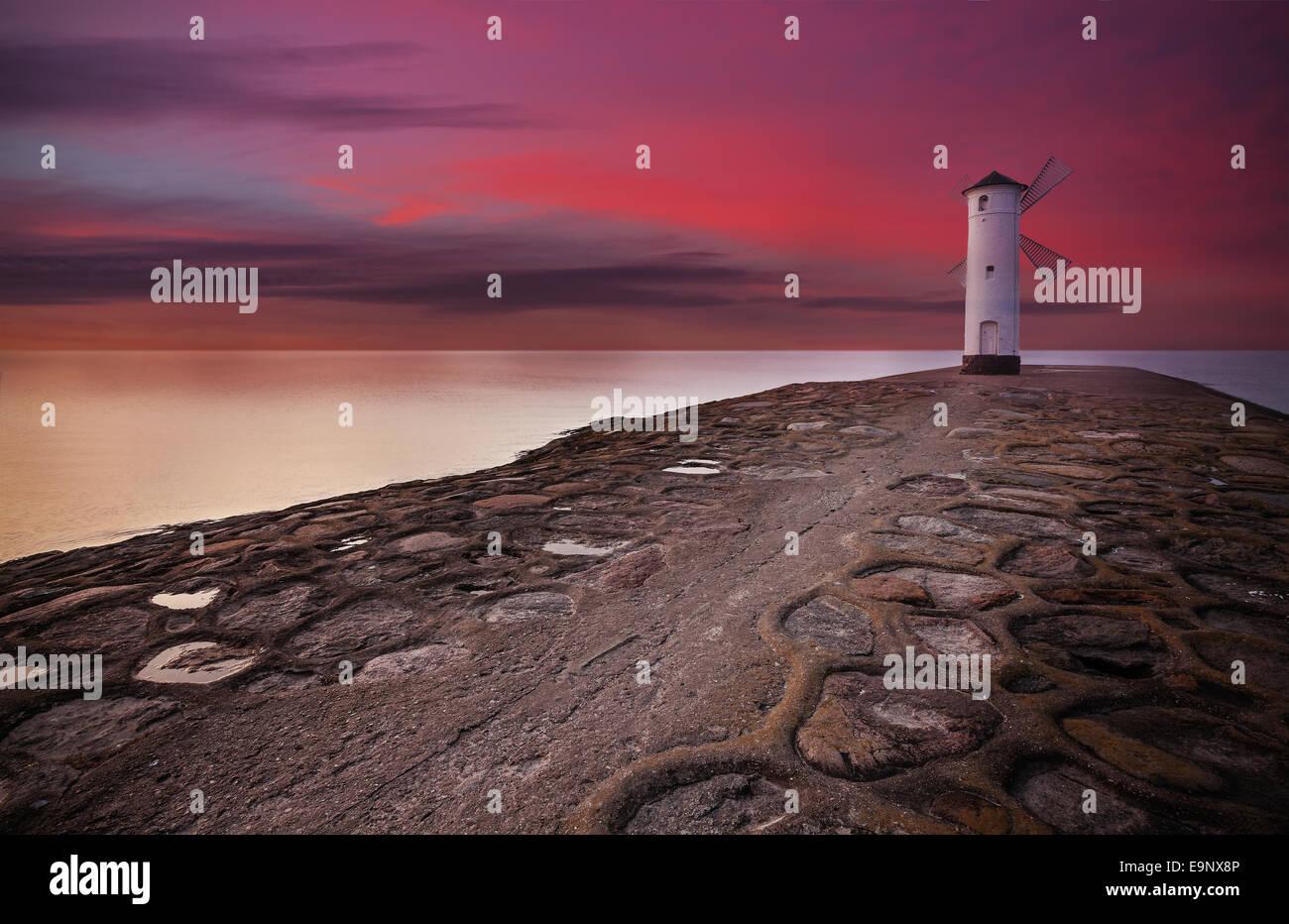 Leuchtturm-Windmühle mit dramatischen Sonnenuntergang Himmel. Stockbild
