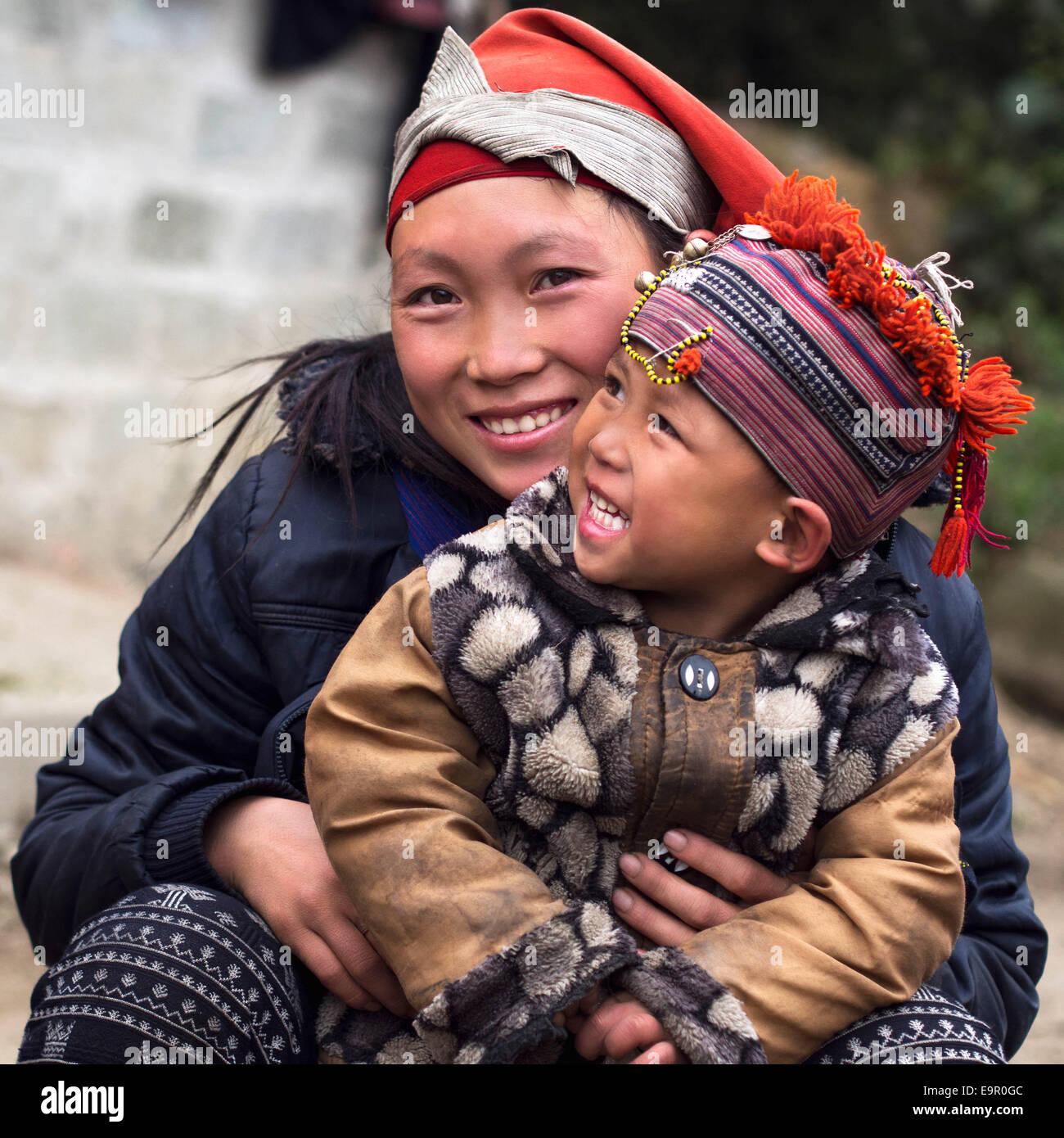 Glückliche Hmong Frau und Kind Lächeln, draußen zu sitzen, an Giang Ta Chai Dorf in der Nähe Stockbild