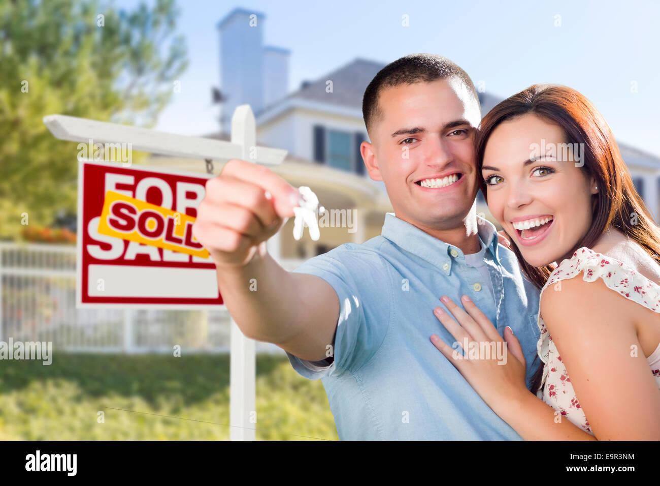 Gemischte Rassen aufgeregt militärische paar vor neuen Domizil mit neuen Hausschlüssel und verkauft Immobilien Stockbild