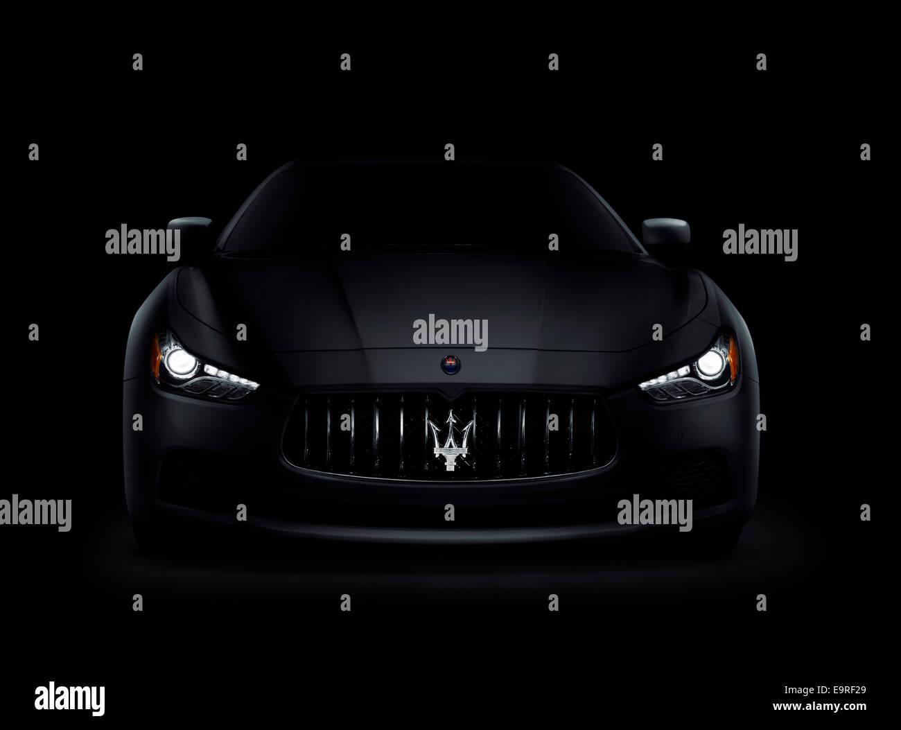 Dramatische Foto einer dunklen 2014 Maserati Ghibli S Q4 Luxus Auto Front anzeigen mit leuchtenden Scheinwerfer Stockbild
