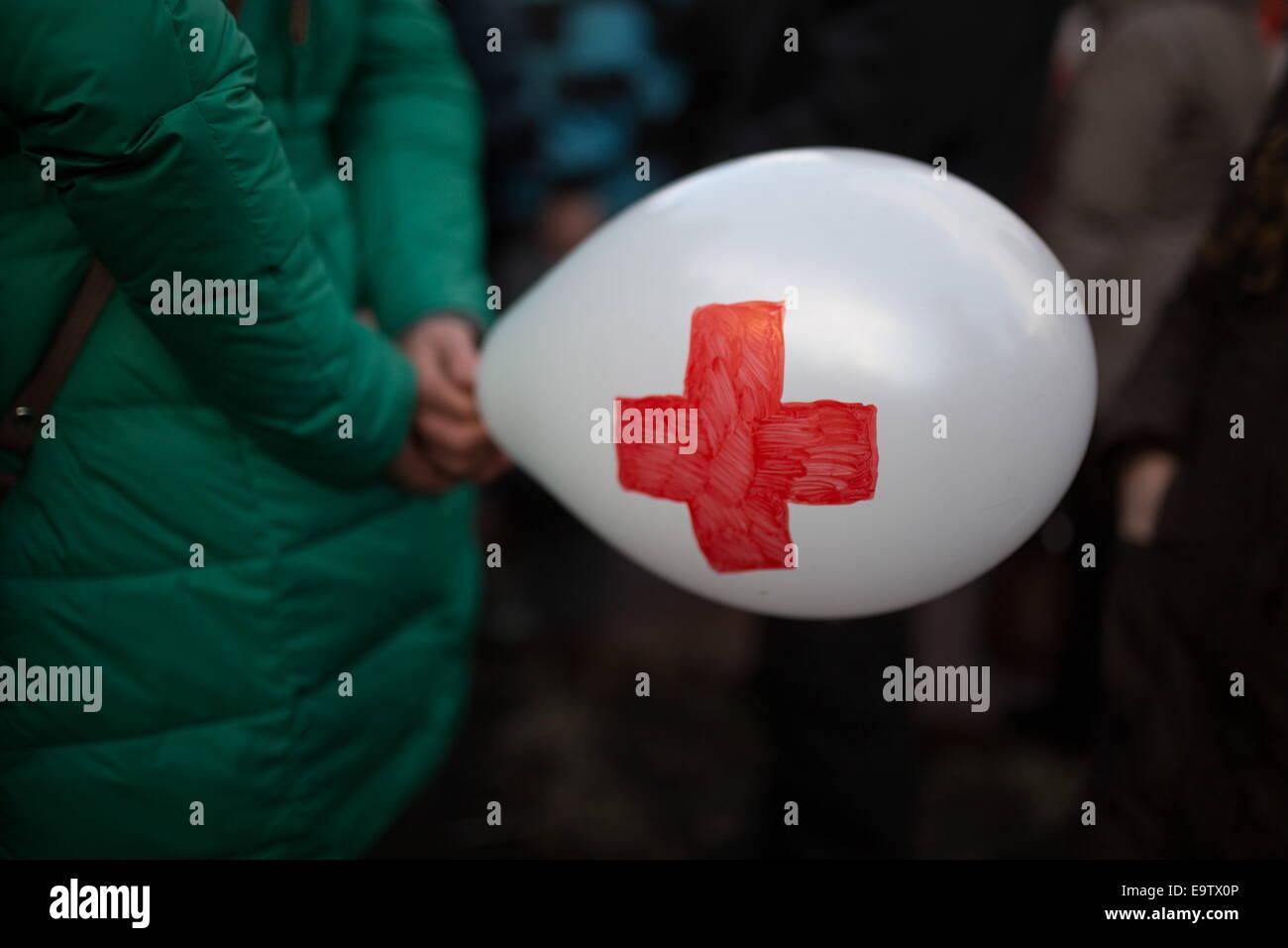 Moskau, Russland. 2. November 2014. Ein Demonstrant mit einem Ballon mit einem roten Kreuz während einer Protestaktion Stockbild