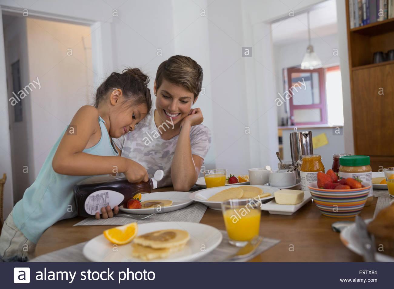 Mutter Tochter Gießen Sirup auf Pfannkuchen beobachten Stockbild