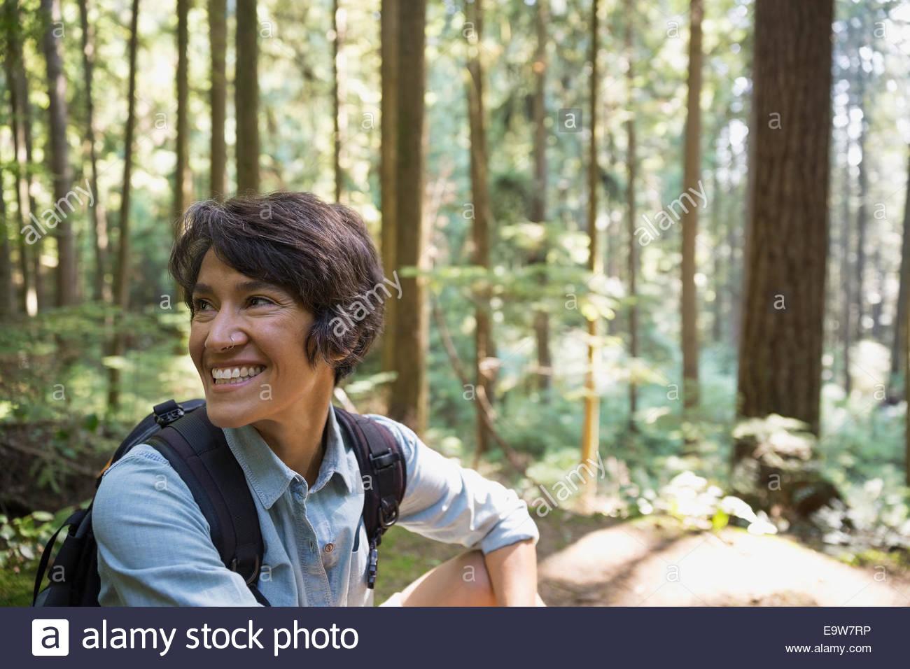 Lächelnde Frau, die auf der Suche über die Schulter in Wäldern Stockbild