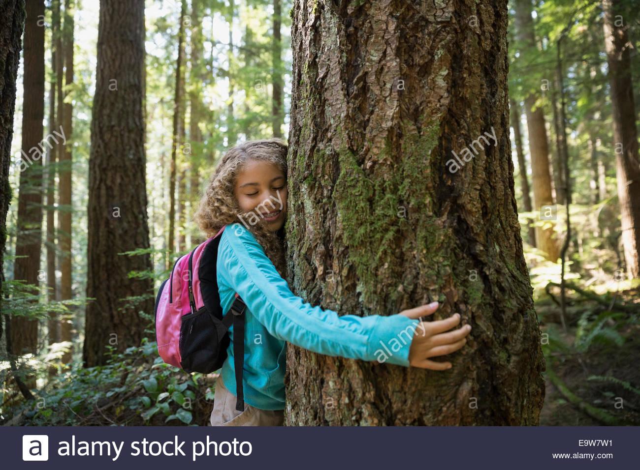 Mädchen mit Rucksack umarmt Baumstamm im Wald Stockbild
