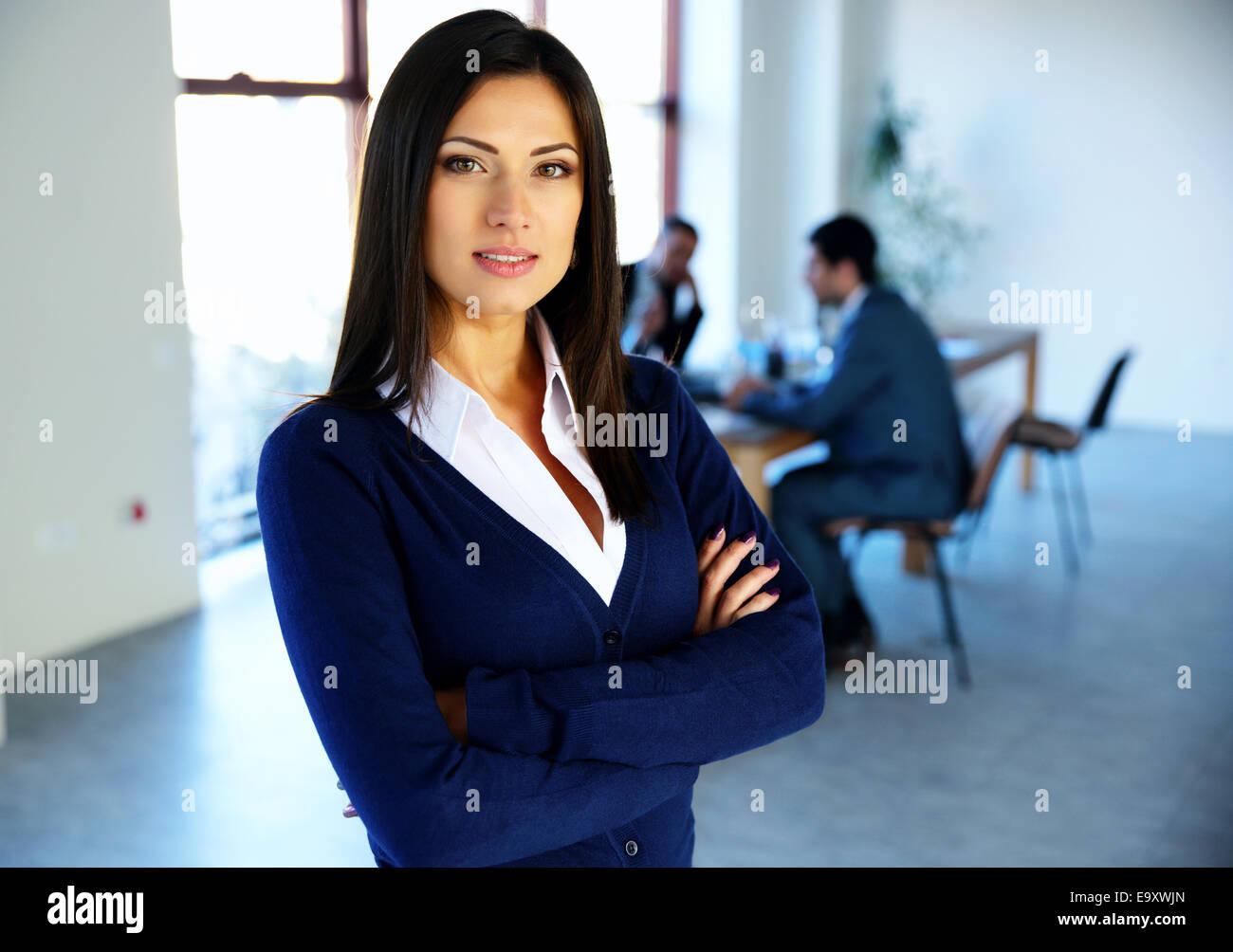 Schöne Frau mit Arme verschränkt mit Kolleginnen und Kollegen im Hintergrund Stockbild