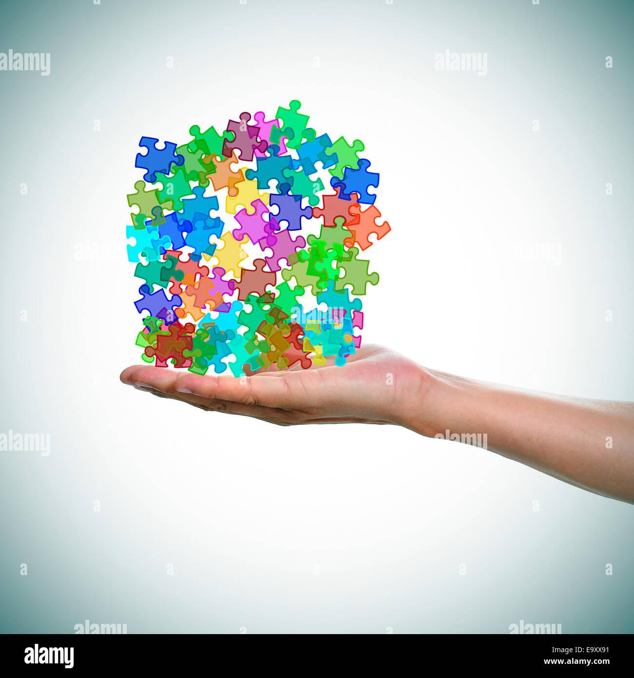 eine Hand des Mannes mit einem Haufen von Puzzle-Teile in verschiedenen Farben als Symbol für den Autismus Stockbild
