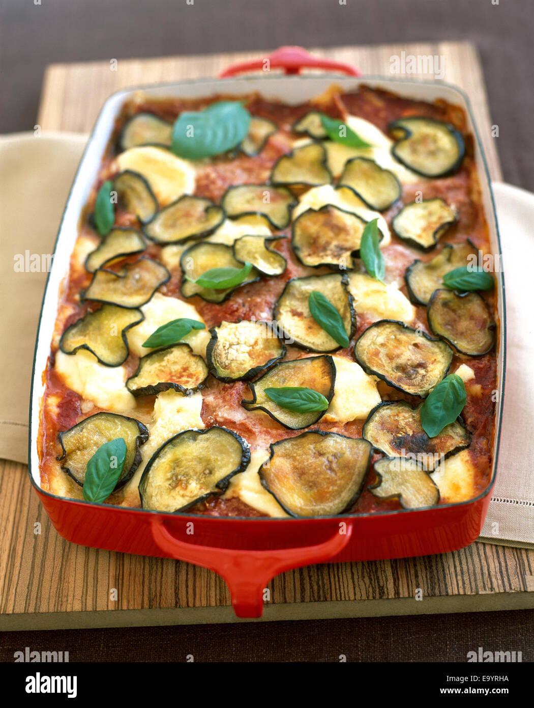 gebackene Lasagne in rot Pfanne mit Auberginenscheiben und Basilikumblätter Stockbild