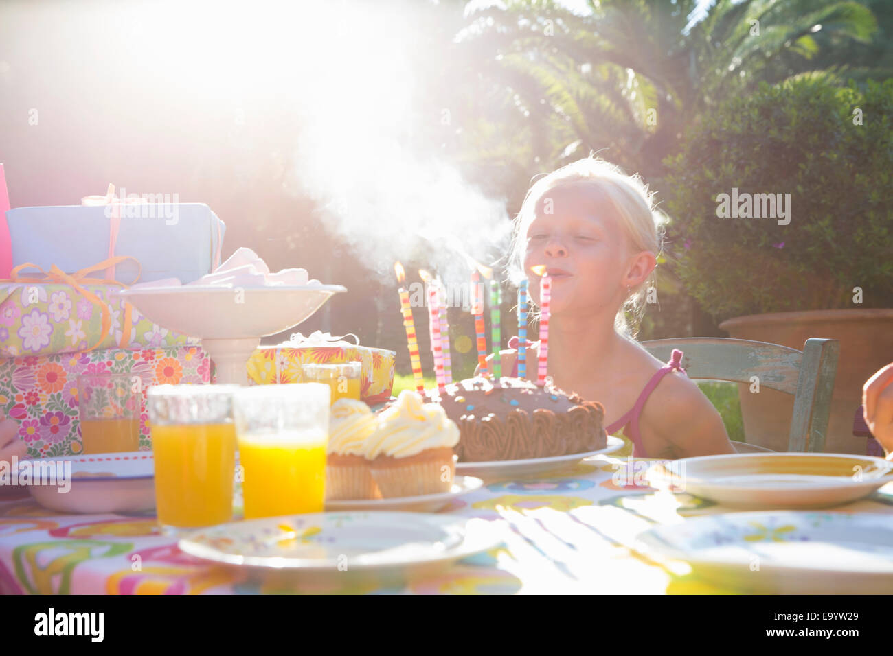 Mädchen bläst Kerzen auf Geburtstagskuchen Stockbild
