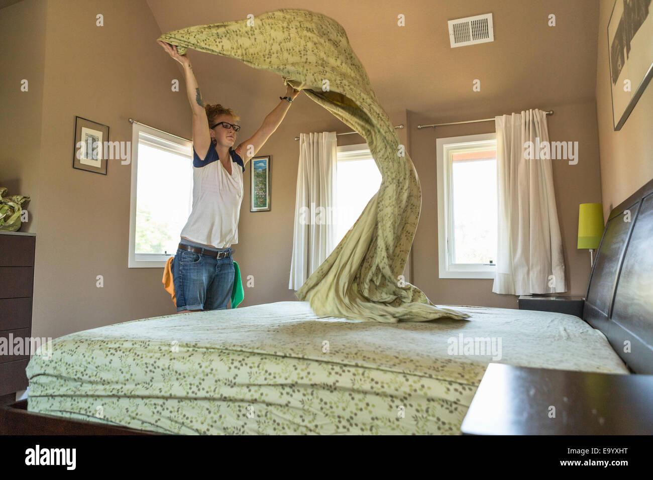 Junge Frau, die Schlafzimmer mit grünen Reinigungsmittel Reinigung Stockbild