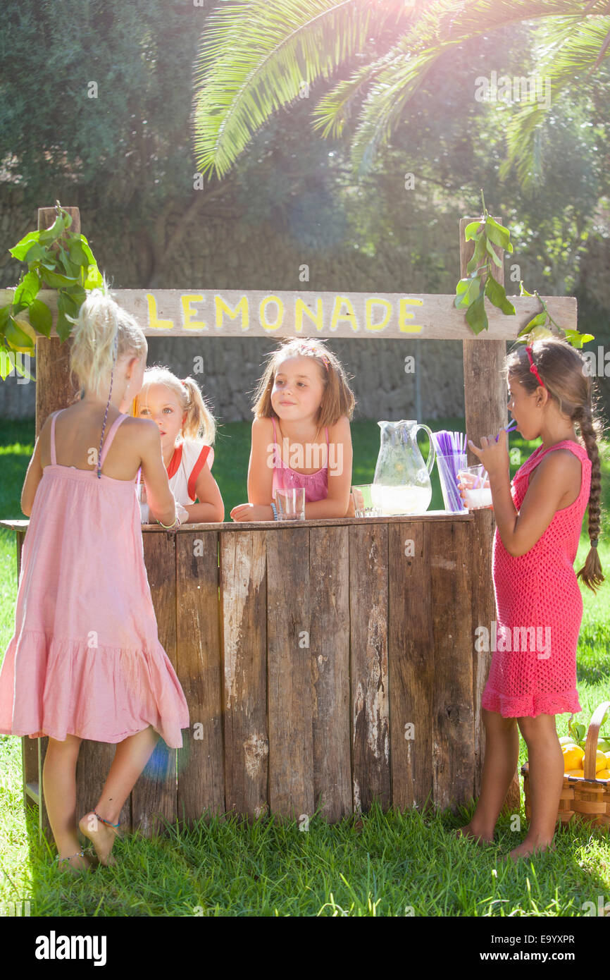 Vier Mädchen, Kauf und Verkauf zur Limonade stehen im park Stockbild