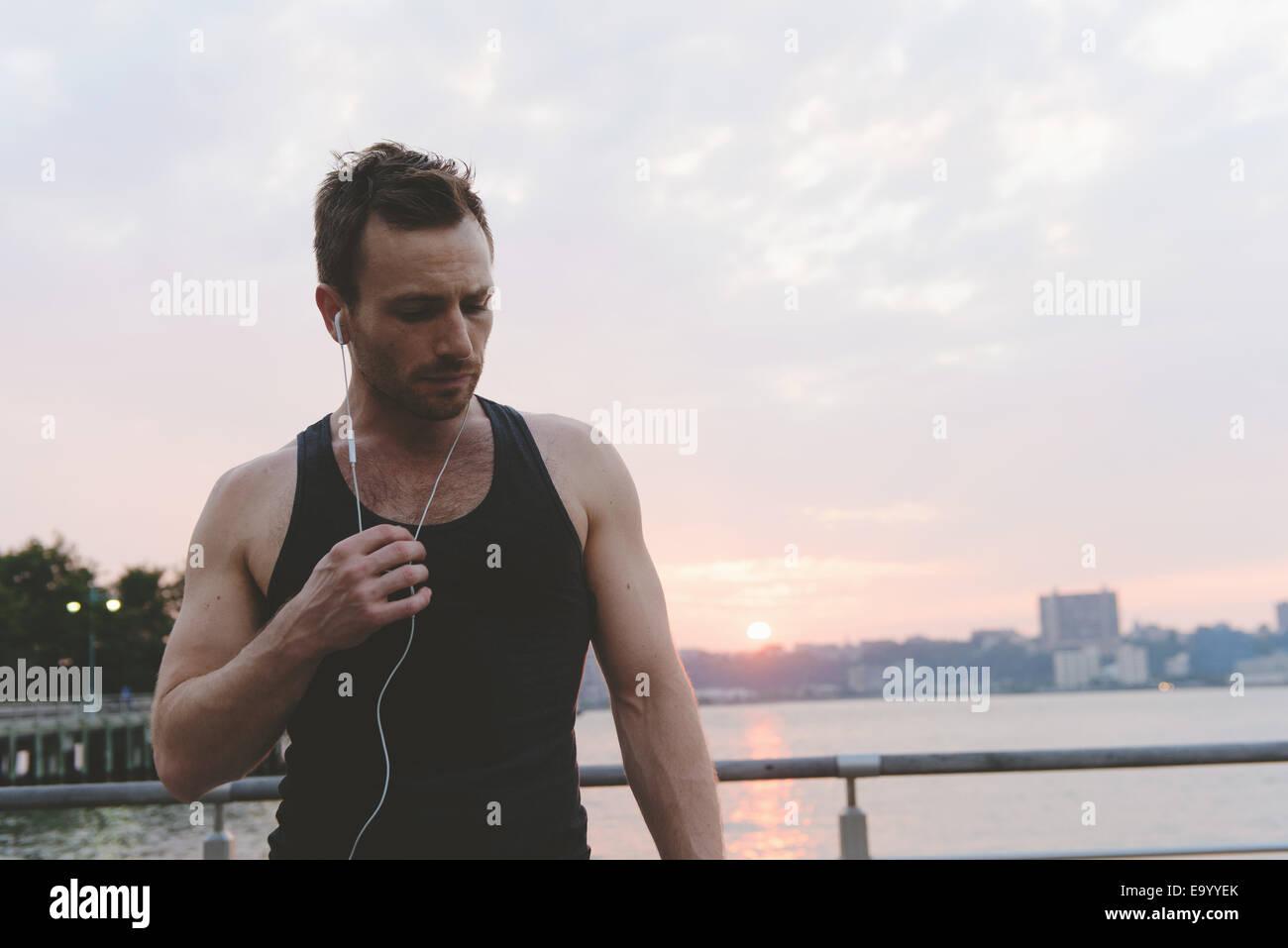 Junge männliche Läufer hören Kopfhörer am Ufer bei Sonnenaufgang Stockbild