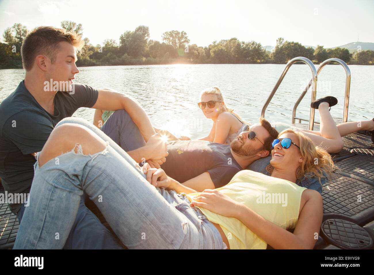 Vier junge Erwachsene Freunde im Chat am Flussufer pier Stockbild