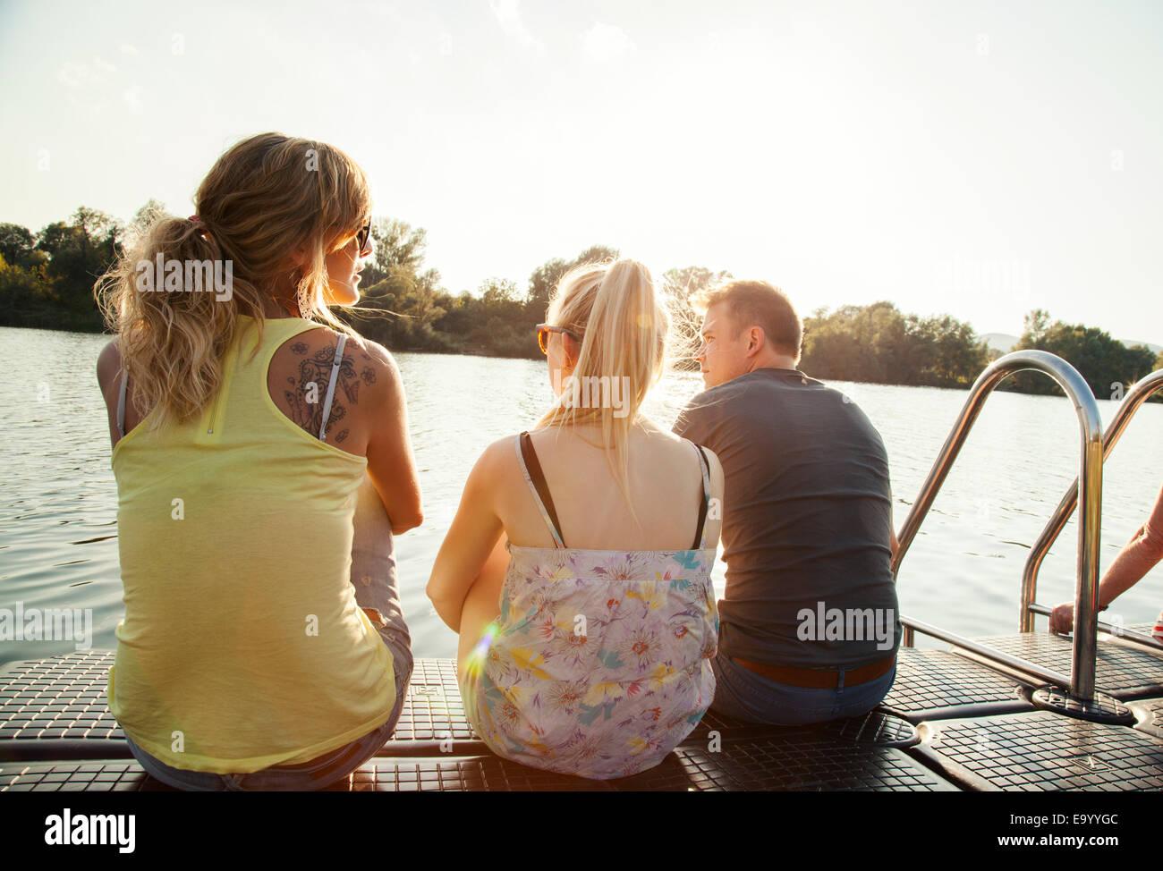Drei junge Erwachsene Freunde blicken Sie von riverside pier Stockbild