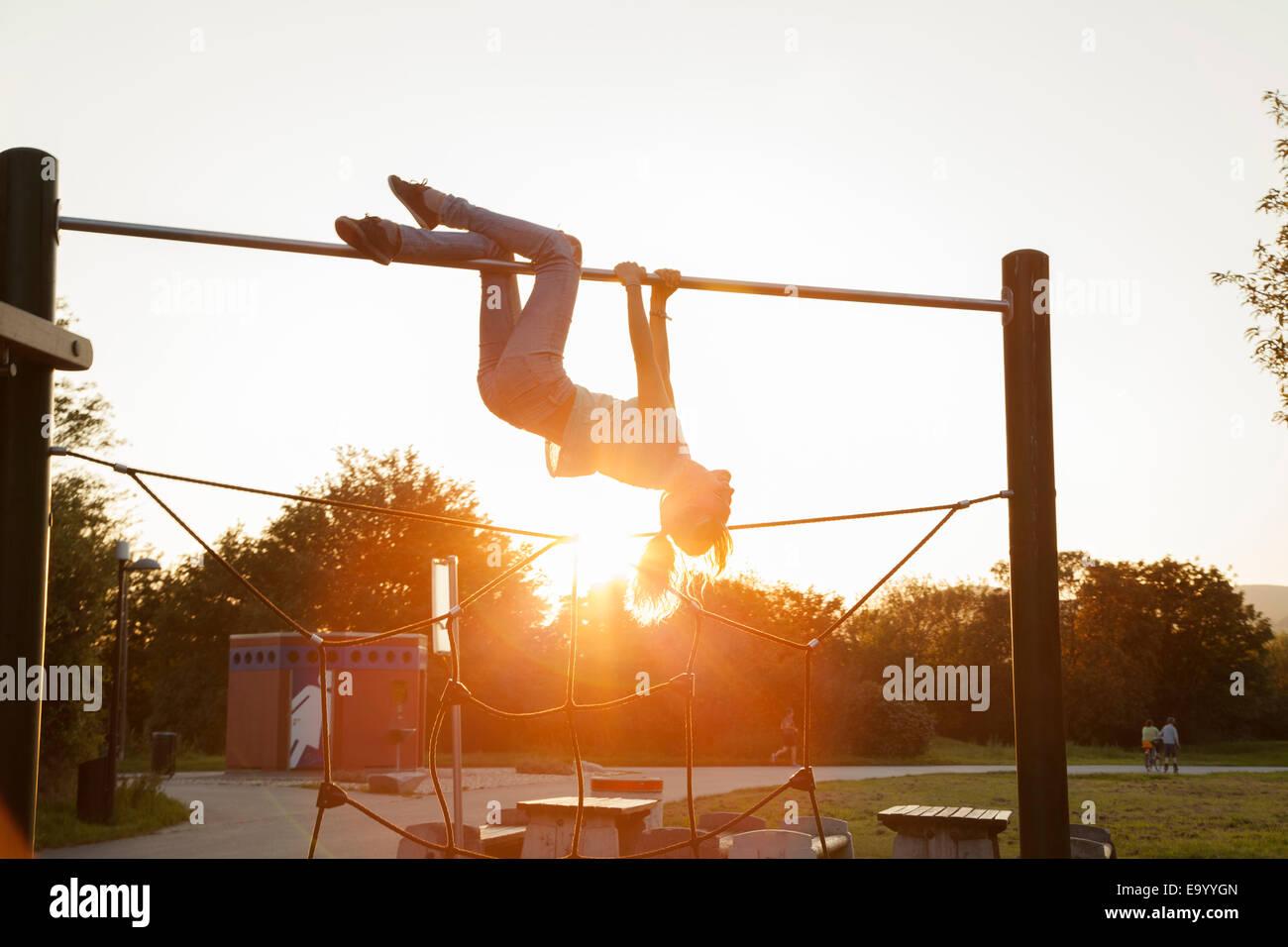 Klettergerüst Erwachsene : Junge frau silhouette auf dem kopf stehend spielplatz