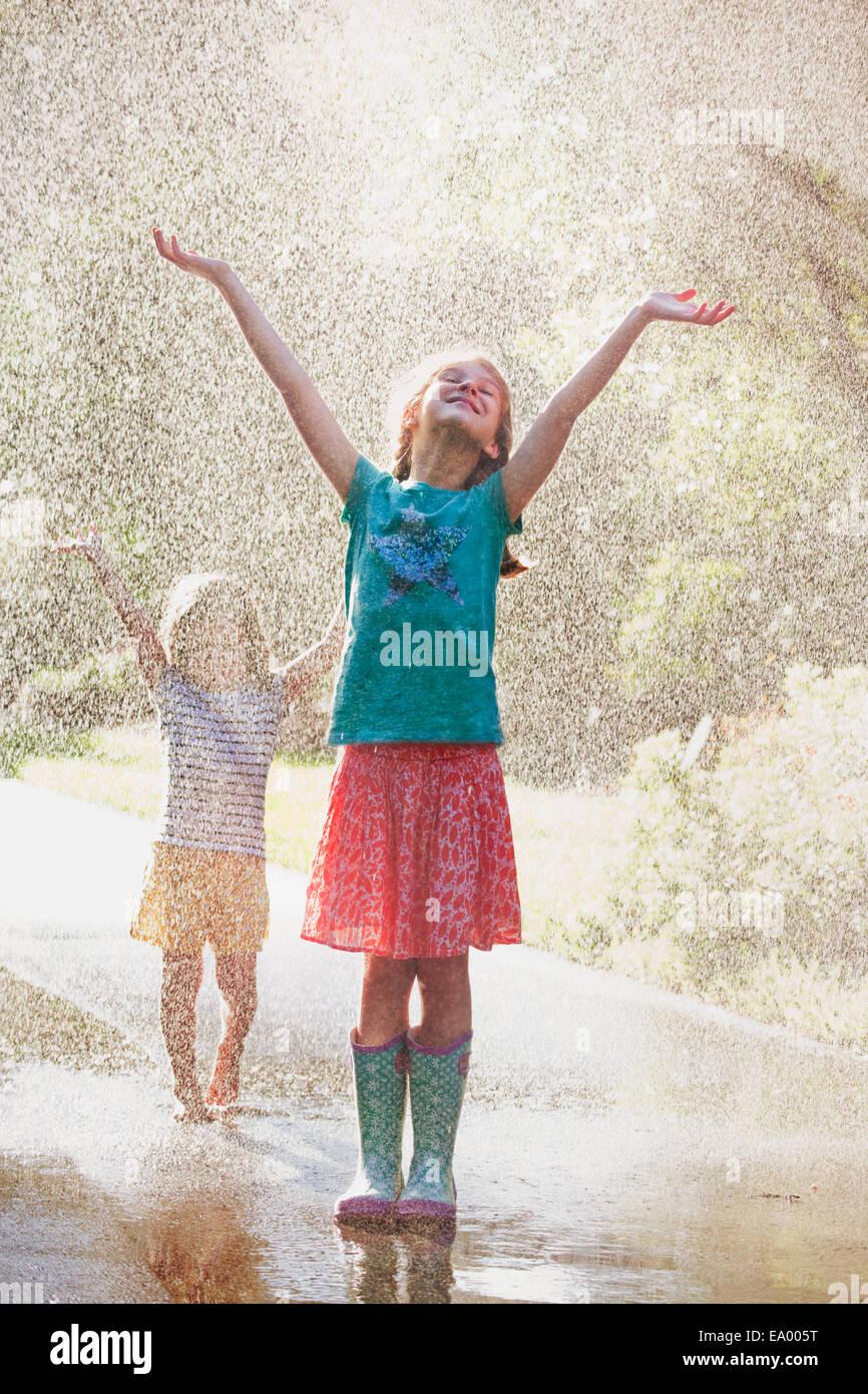 Zwei Mädchen mit Armen öffnen stehen im Wasser-Spray auf Straße Stockbild