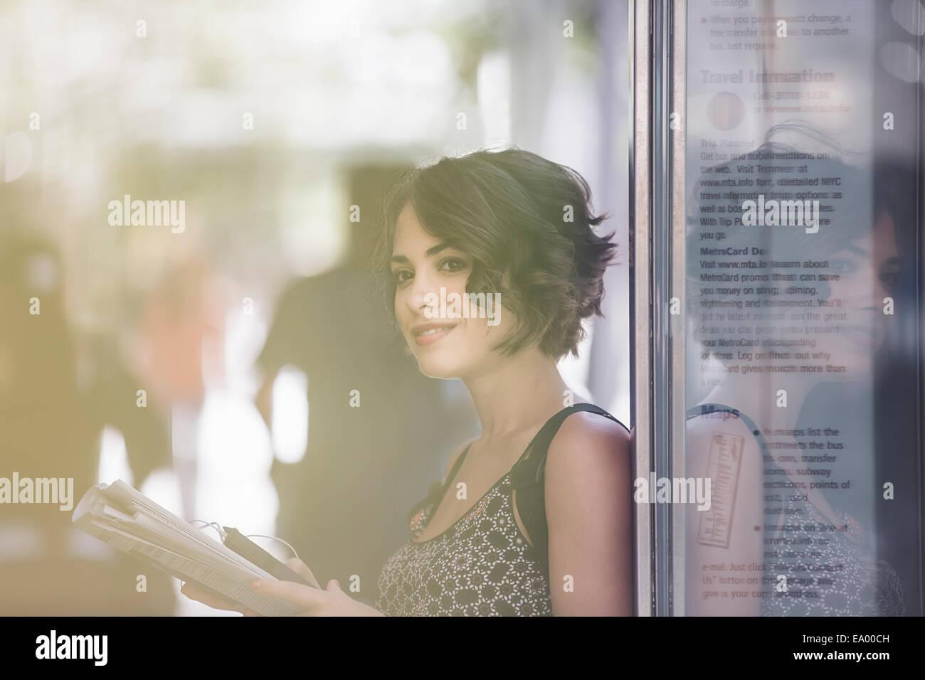 Junge Frau an Bushaltestelle Zeitung lesen und warten auf Bus, New York, USA Stockbild