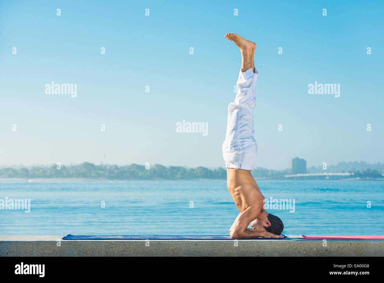Junger Mann praktizierender Upside-down Yogaposition am Pacific Beach, San Diego, Kalifornien, USA Stockbild