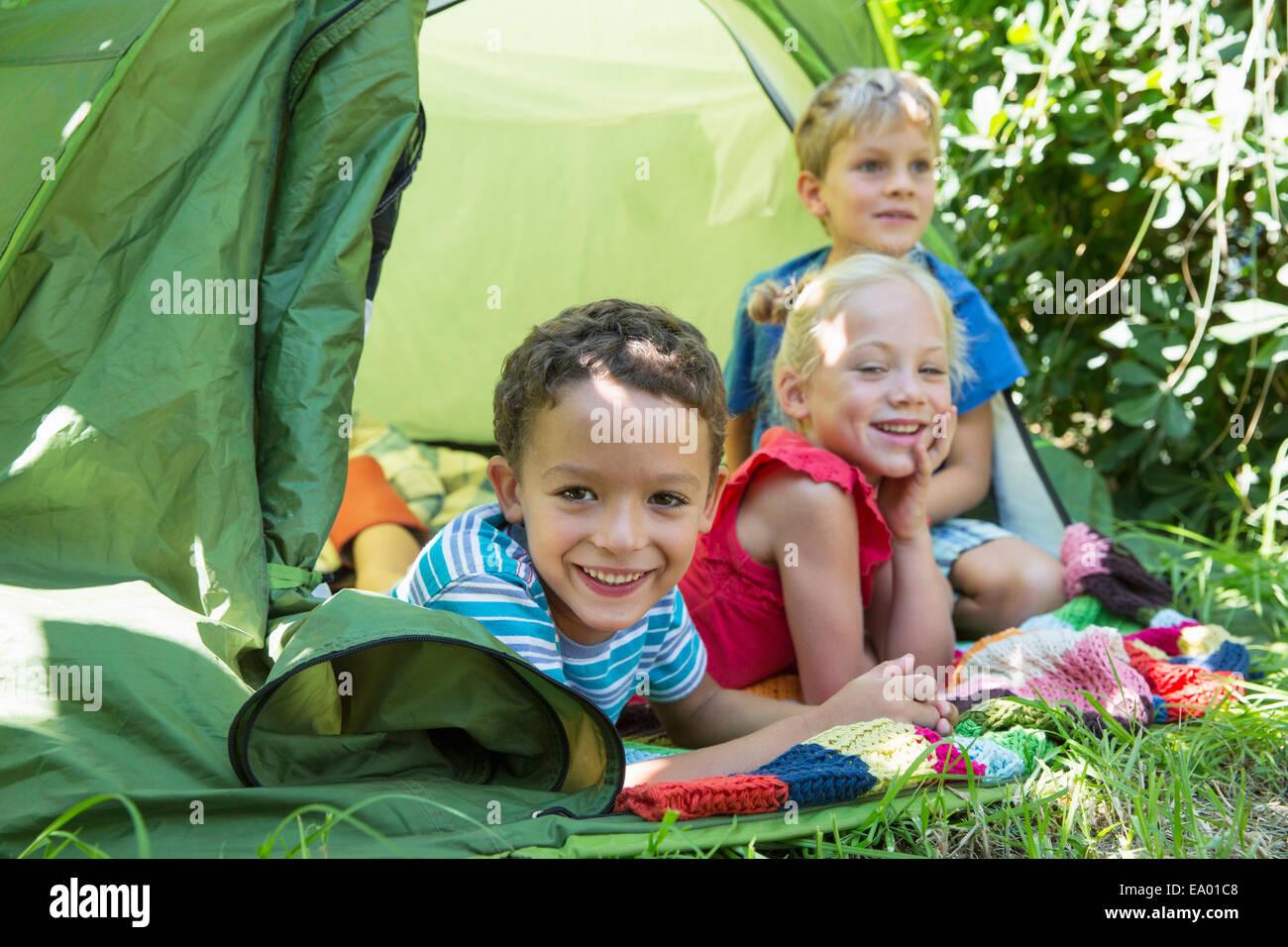 Porträt von drei lächelnden Kindern liegen im Gartenzelt Stockfoto