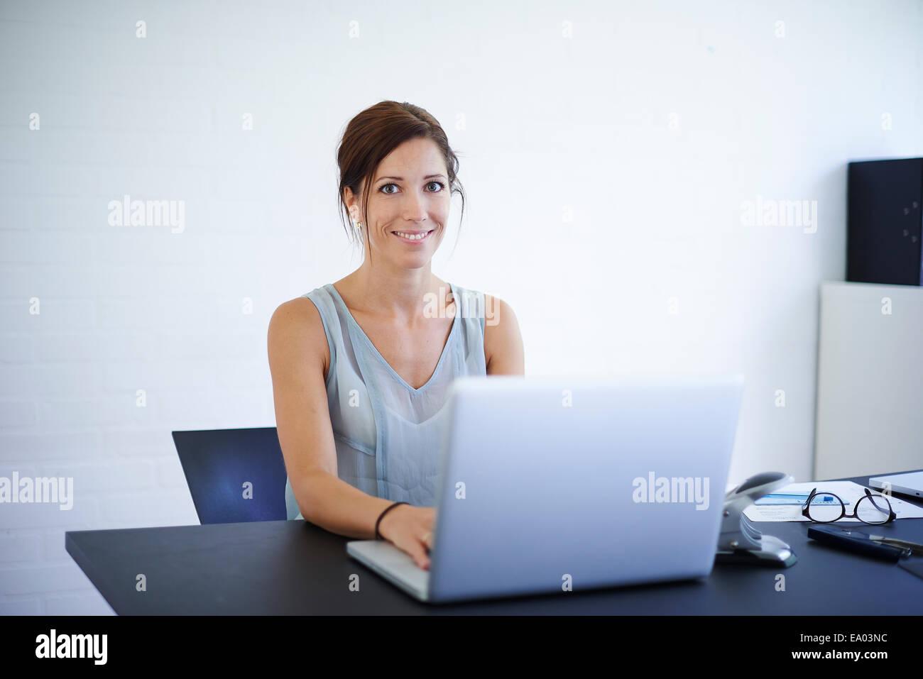 Porträt Mitte Erwachsene Frau an Laptop von zu Hause aus arbeiten Stockbild