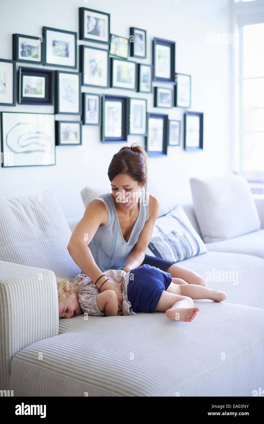 Mitte Erwachsene Mutter kitzeln Kleinkind Tochter auf sofa Stockbild