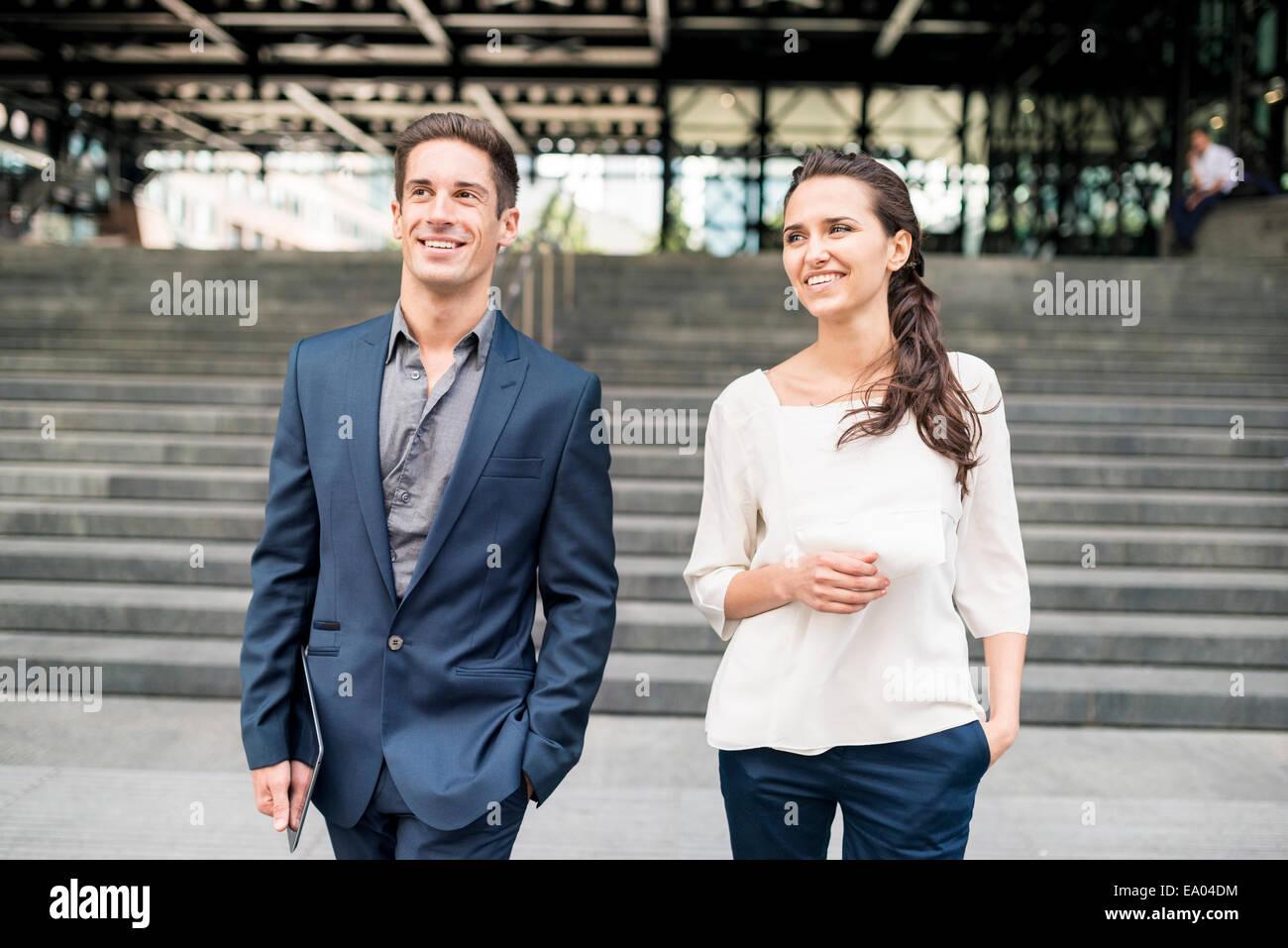 Geschäftsfrau und Mann im Chat beim gehen, London, UK Stockbild