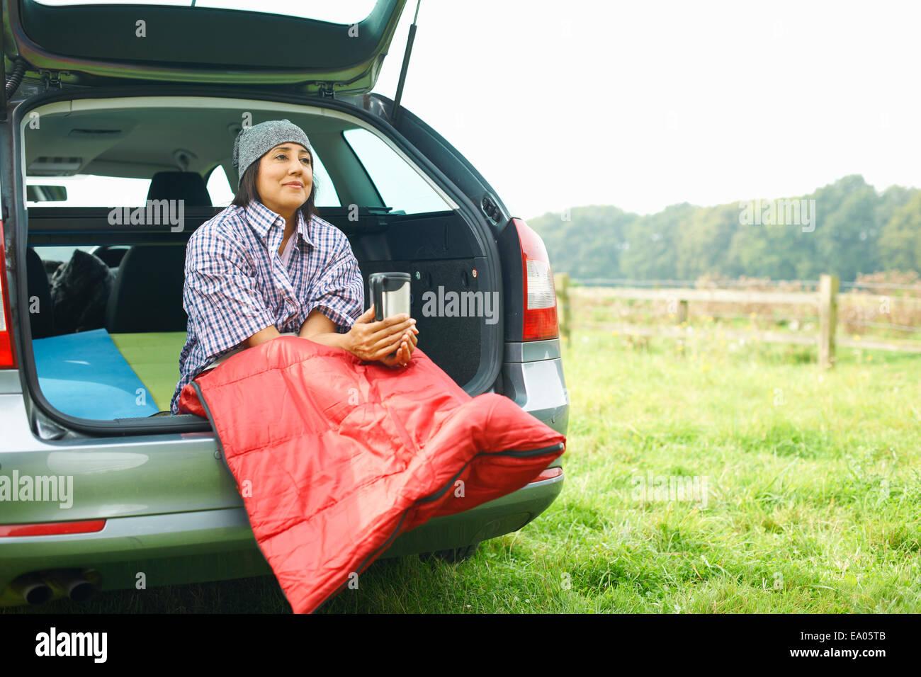 Frau sitzt am Heck des Autos mit Beinen versteckt im Schlafsack Stockbild
