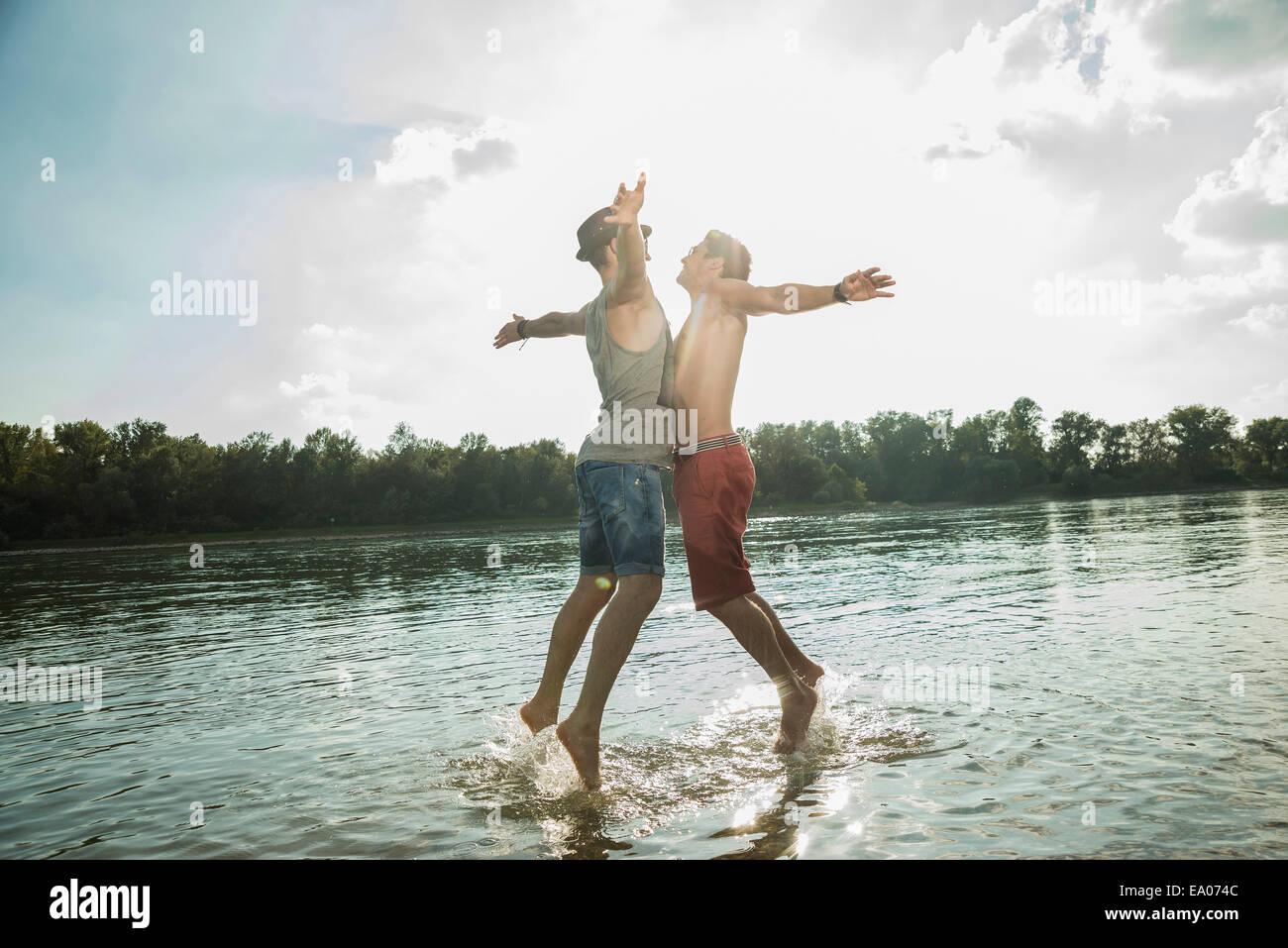 Junge Männer Brust stoßen in See Stockbild