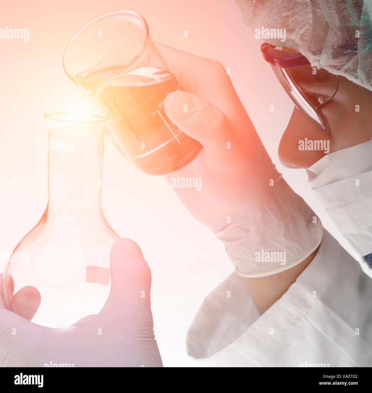 Chemiker Gießen Flüssigkeit aus Becher in Flasche Stockbild