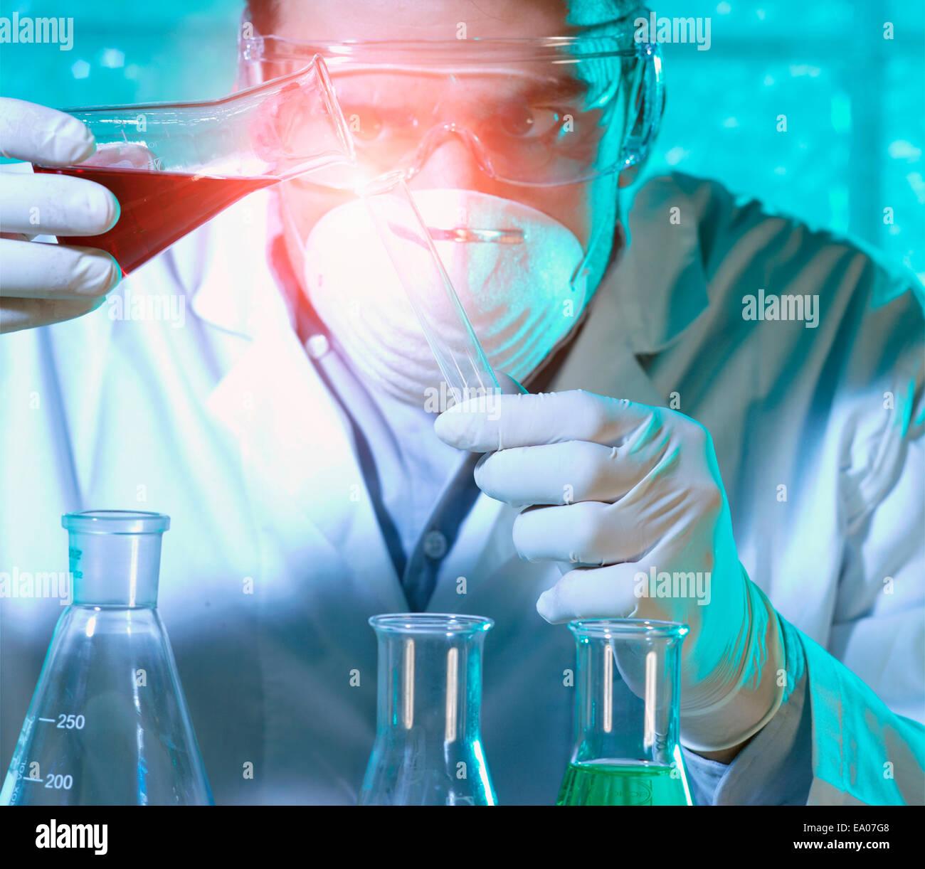 Chemiker Gießen Flüssigkeit aus Becher in Reagenzglas Stockbild