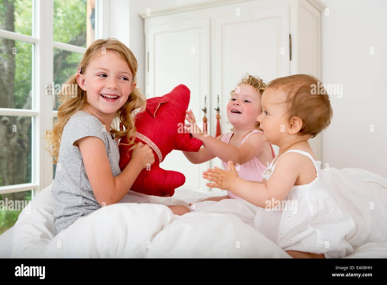 Drei Mädchen auf dem Bett mit weichen Spielzeug spielen Stockbild