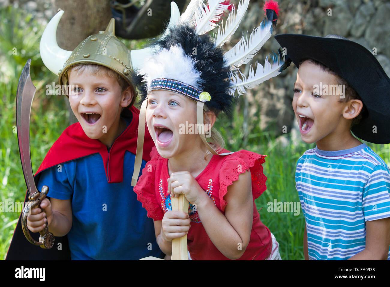 Drei Kinder tragen Fancy Dress Kostüme, spielen im park Stockbild