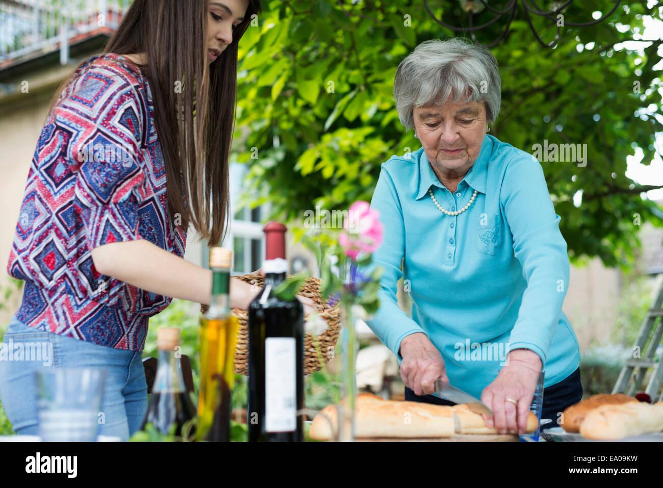 Ältere Frau Schneiden von Brot Stockbild