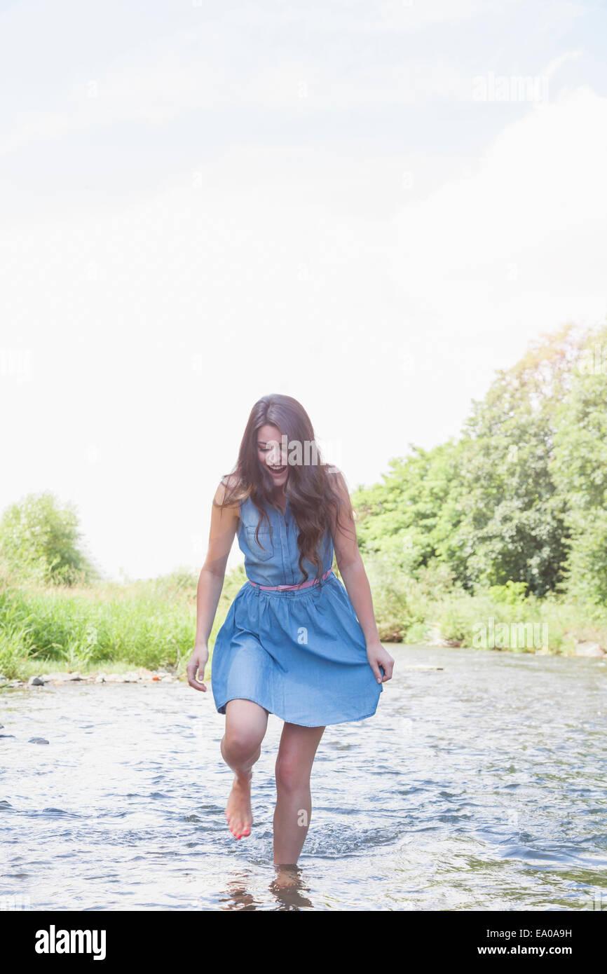Junge Frau in seichten Bach Stockfoto